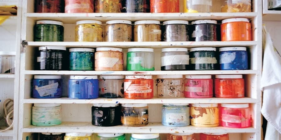 Shelves of coloured paint pots
