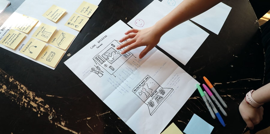 A student draws concepts on a desk filled with paper and post-it notes.