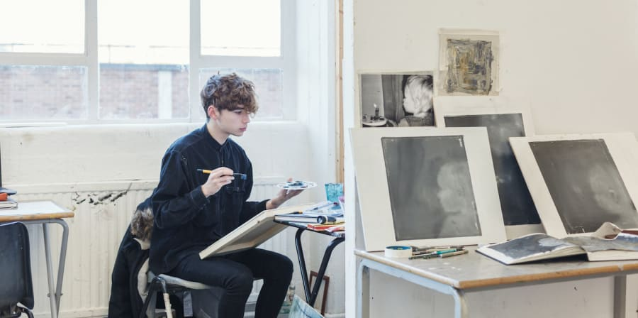 A student sat down painting
