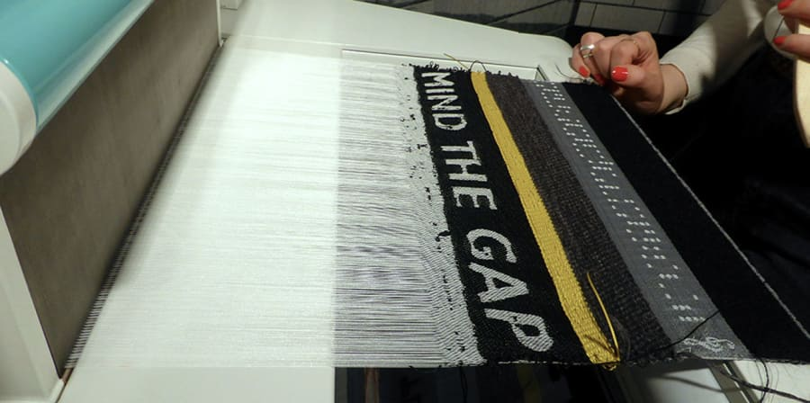 A fabric being woven on a loom that reads 'MIND THE GAP