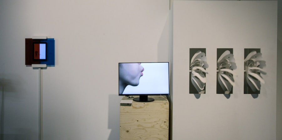 Still image of a video installation of a mouth blowing three paper turbines on the wall beside the screen