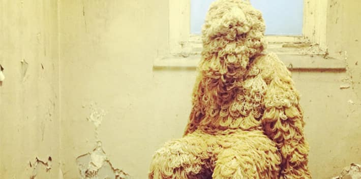 Image of a wooly human figure sat on a chair in a dilapidated room