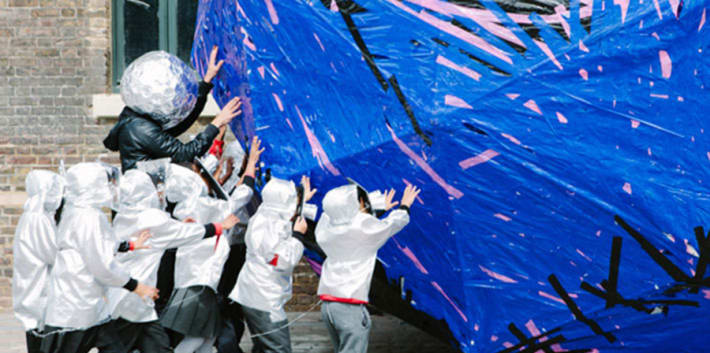 Children in white boiler suits pushing large blue ball
