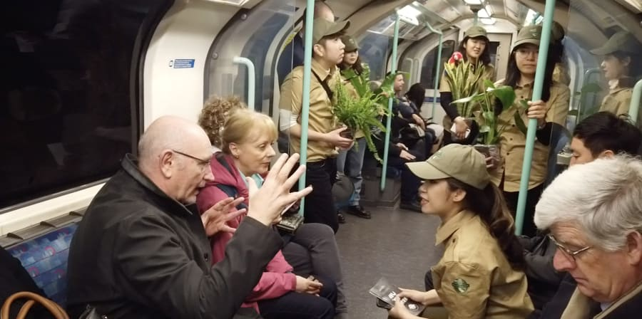 Students dressed as park rangers engage the travelling public in converesation on a tube train