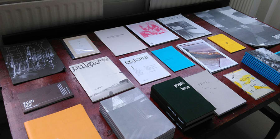 A table is filled with a range of independent arts publications.
