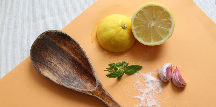 A wooden chopping board covered with a wooden spoon, herbs and half a lemon.