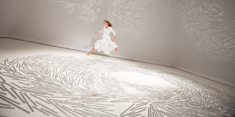 A person running around a room in a white dress. The floor of the room is covered in white marks.