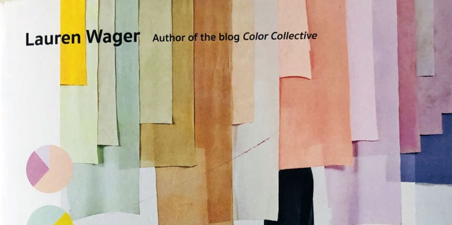 A single figure walks across a gallery space filled with hanging colour banners.