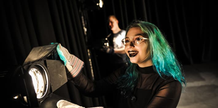 Green-haired girl operating a stage light