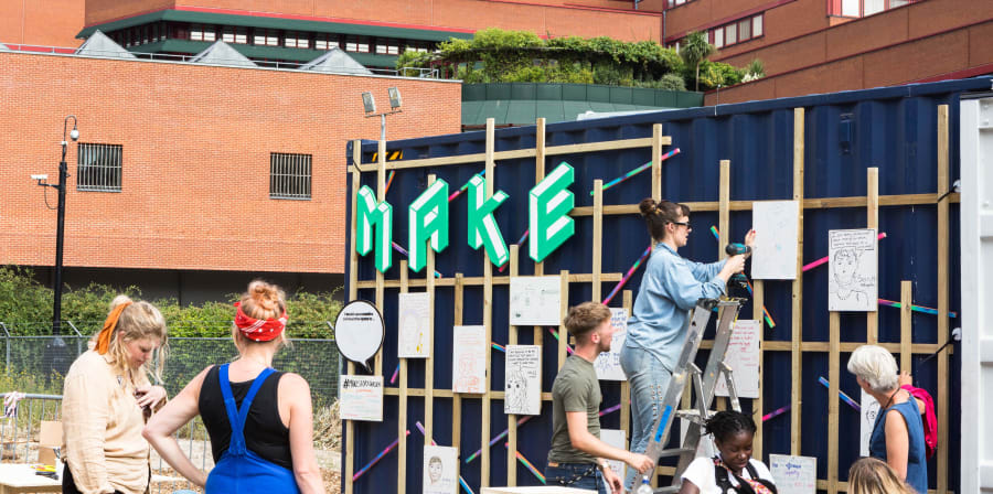 Exterior of Make space with people on ladders and view of British Library
