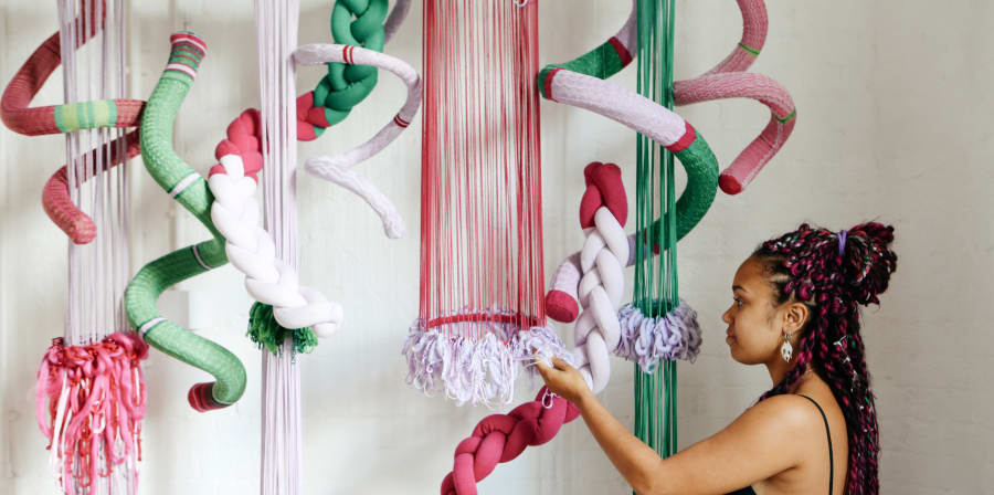 Girl interacting with a textiles installation that hangs for the ceiling