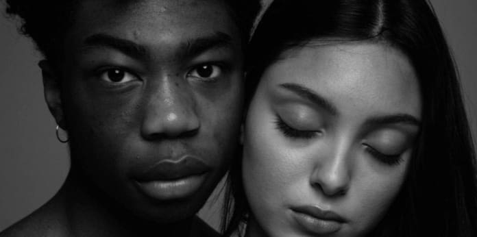 A black and white photograph of two models, one of whom has closed their eyes.