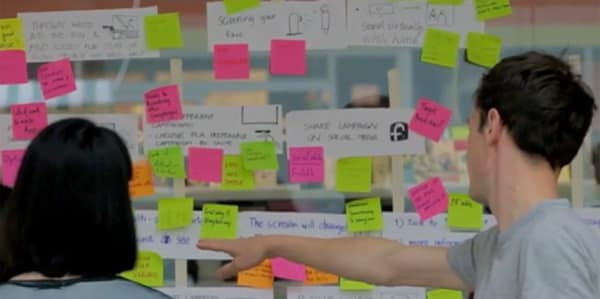 Students using colourful post-it notes to map out ideas for the design of a petition for Plan International UK.