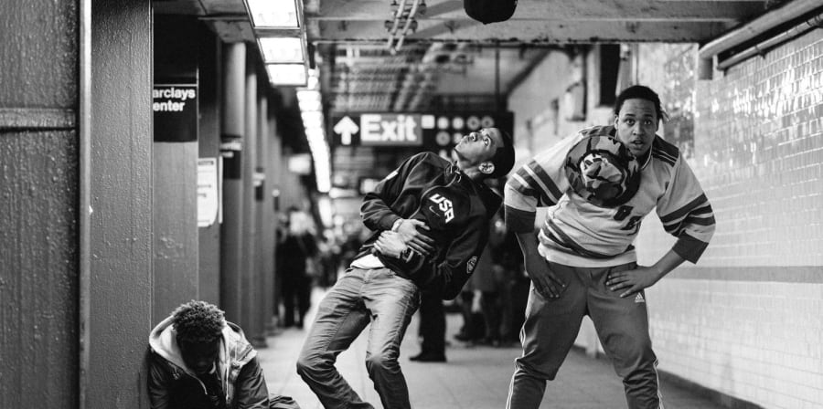 3 male street dancers doing a performance on the subway