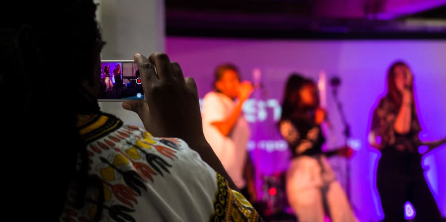 An audience member filming a performance on their phone