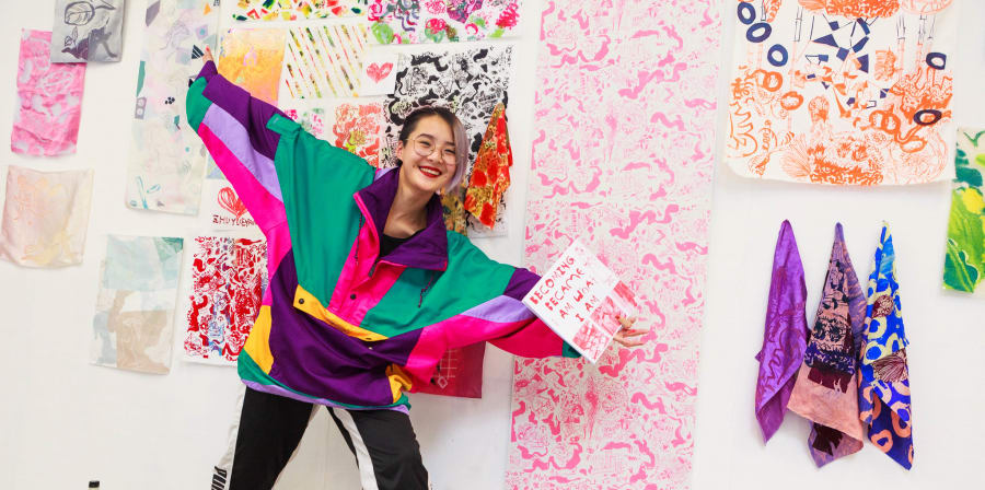 Student posing in front of her textile design work samples.