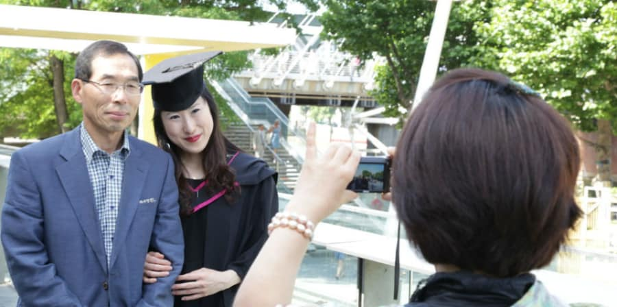 A graduate in their graduation gown having a photo taken with their parents.