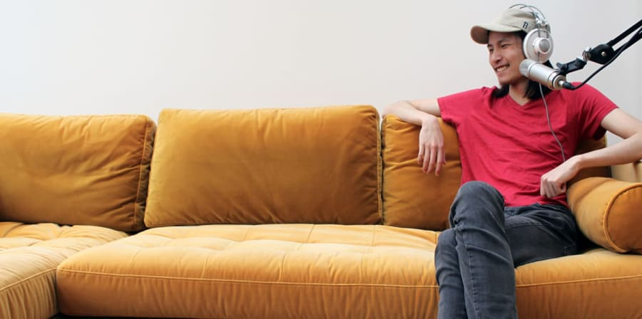Justin sits beside a microphone on a yellow sofa.