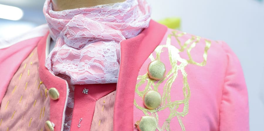 Close up shot of a pink dress coat with gold trim