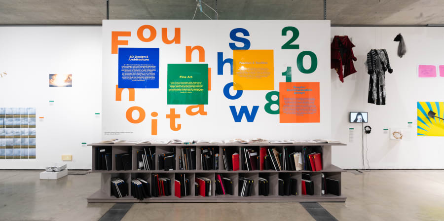 Work on display in a gallery, Foundation Show 2018 is written on the wall is bold green, orange and blue letters