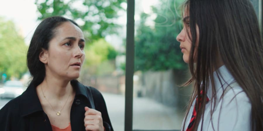 A mother and daughter stare at each other at a bus stop.