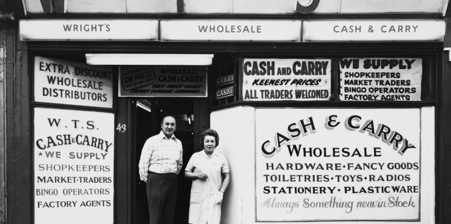 Black and white photo of couple stood outside cash and carry in 1975.