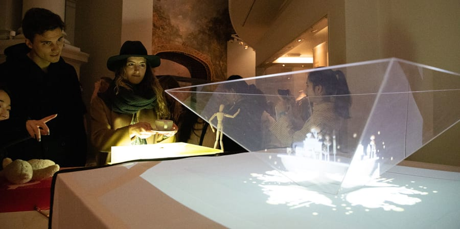 Visitors watch a hologram of student work.