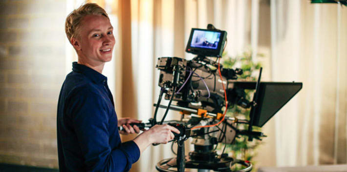 UAL alumin behind a video camera