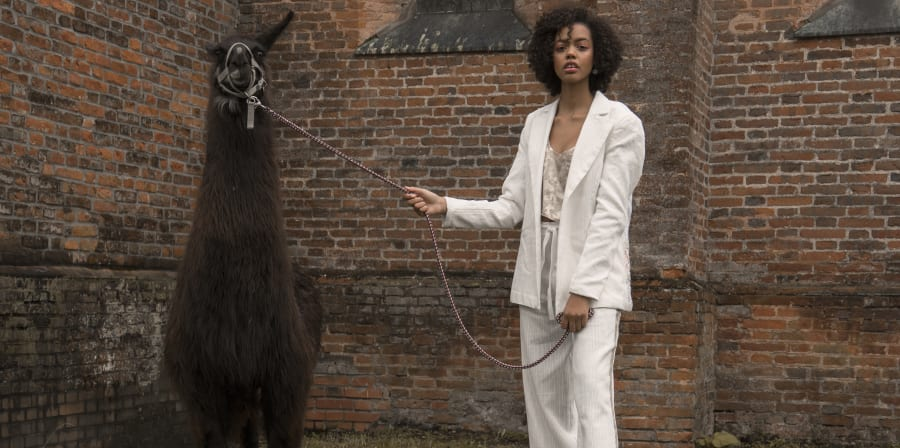 Photograph of female model in a white suit with an alpaca