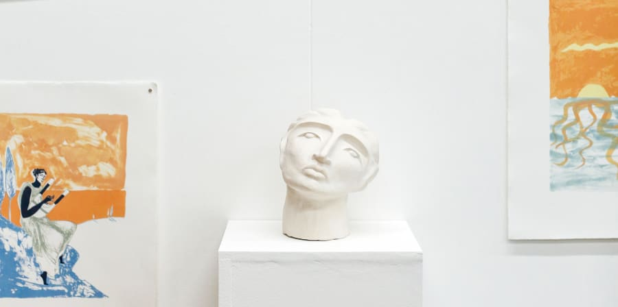 Display of a sculpture of a face and drawings