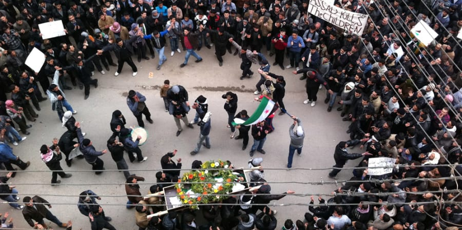 Crowd gathered waving Syrian flag as a body is carried in a coffin.