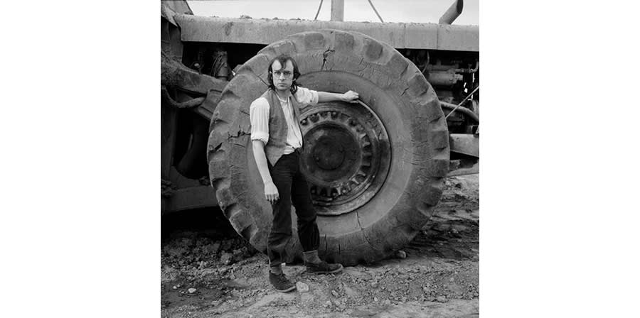 Photograph of a man standing next to a tractor