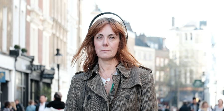 Photo of woman in street holding her phone with headphones on