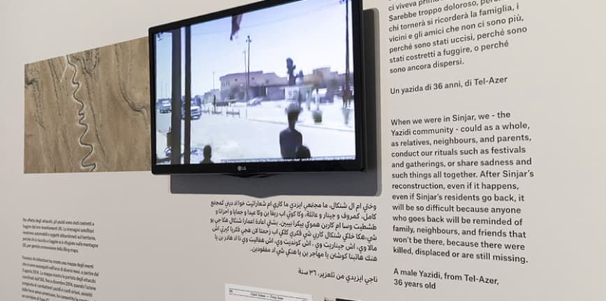 Photo of Maps of Defiance exhibition with screen and text about Sinjar.