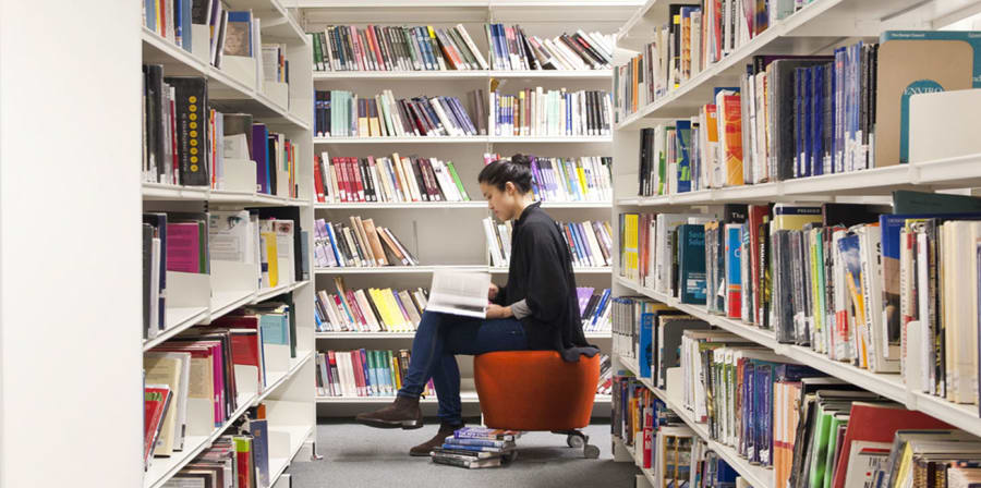 Photo of a girl sat in between two book shelves reading