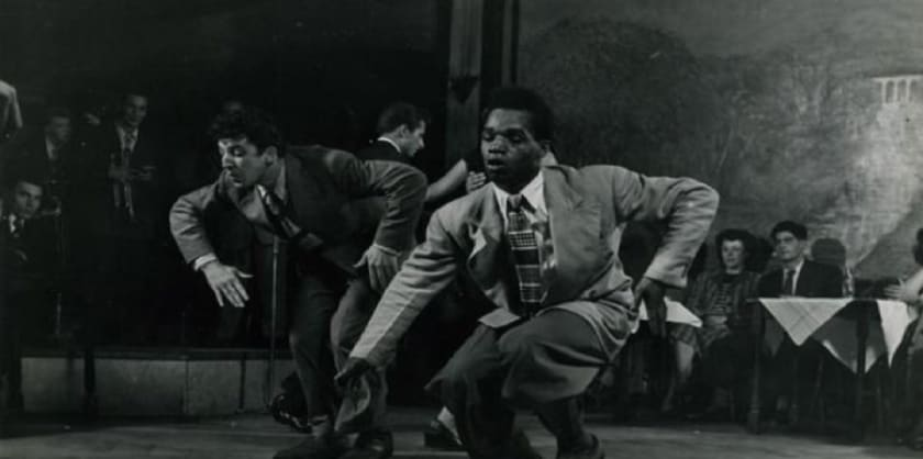 a black and white picture of two men in suits dancing