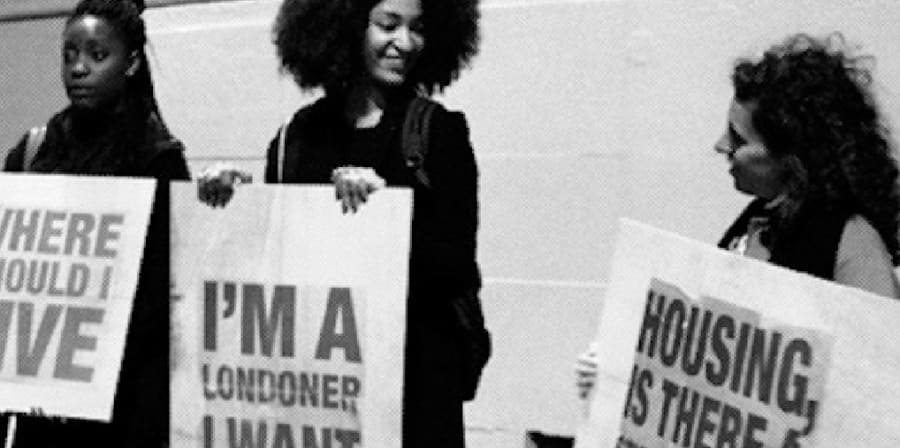 Black and white image of three girls holding up placards