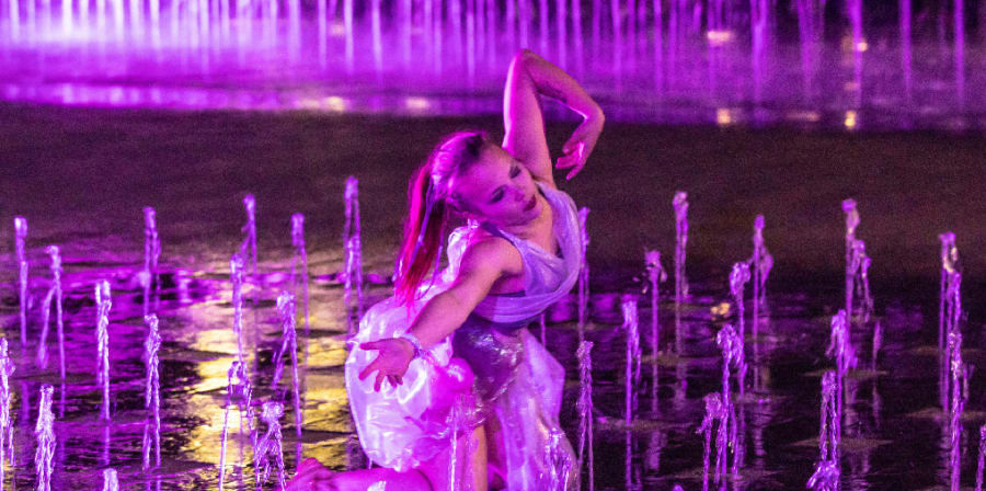 a girl dances in a costume amongst the fountains outside of csm