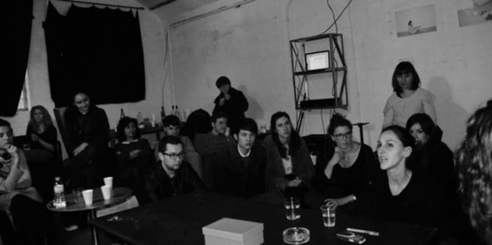 A black and white photograph depicting a discussion at a Salon Flux event.