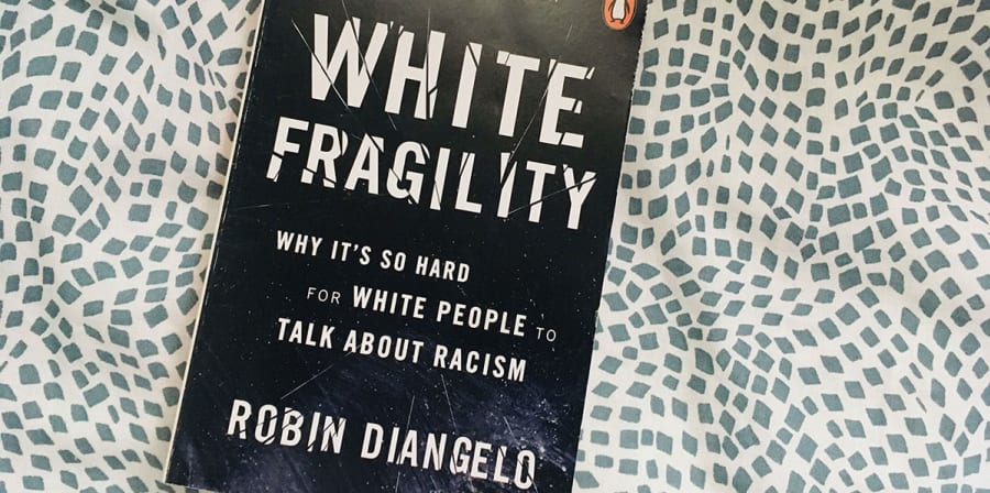 Image depicts White Fragility on a black and white spotted background.