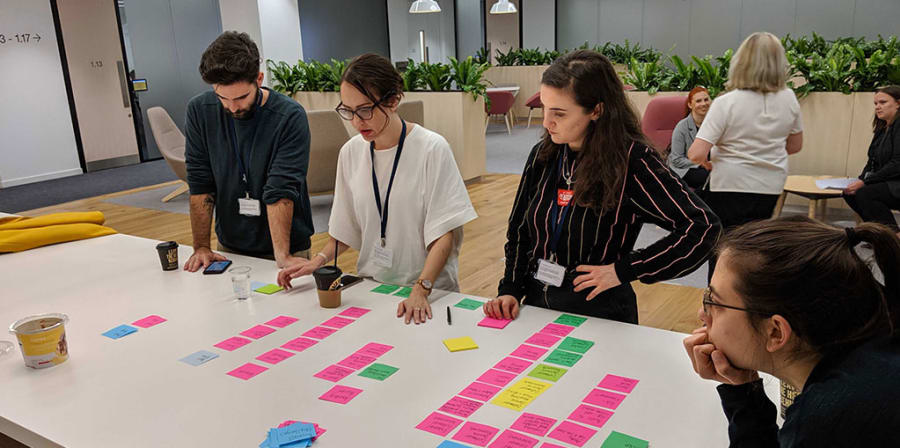 Rafa and his colleagues collaborate on a project over a table of post-it notes.