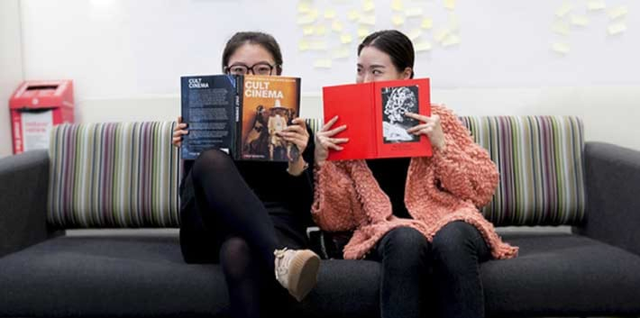 Two students holding books at LCC Library