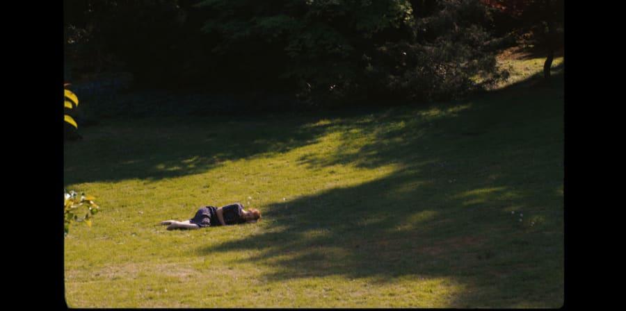 A girl lies on green grass.