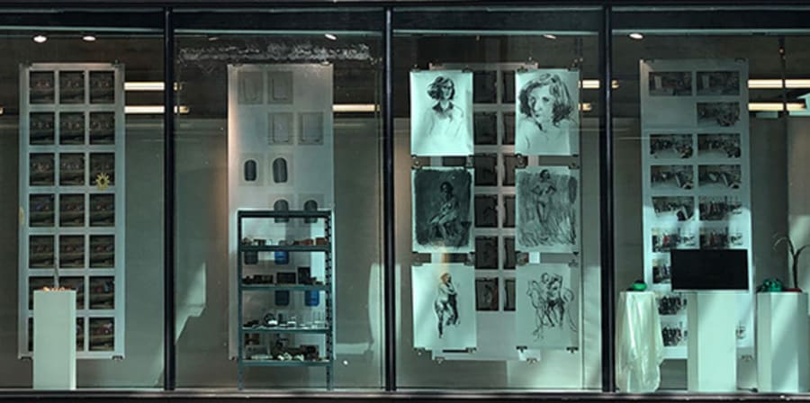 An exhibition of works behind a large window