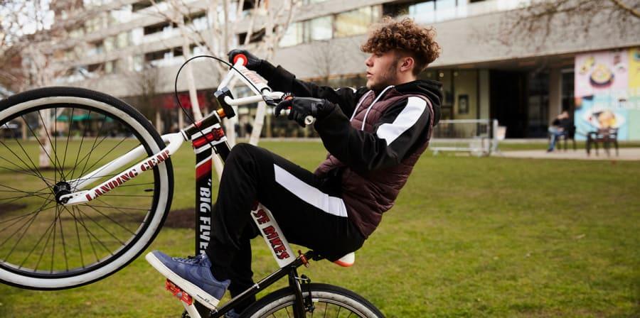 Man doing wheelie on a bike in park