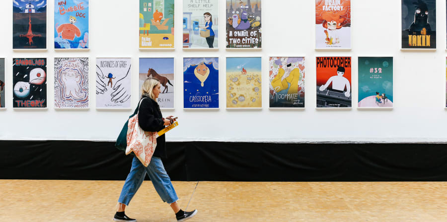 Student walking along a corridor with animated posters on the wall