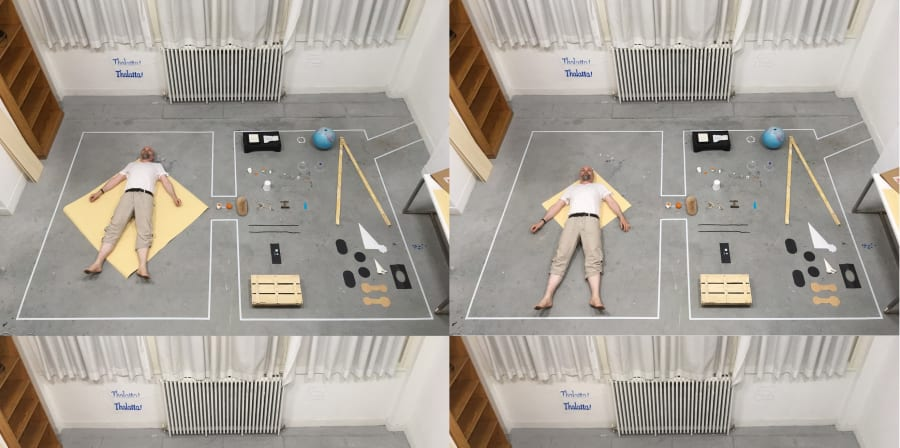 man laying down on studio floor aerial image with work around him