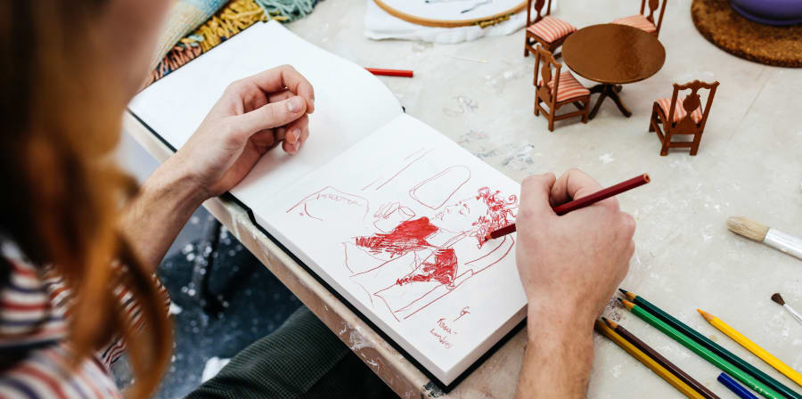 Student sketching at a table
