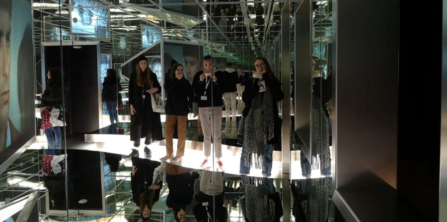Students are reflected on the walls and ceilings of a mirrored exhibition space at the Berlinale.