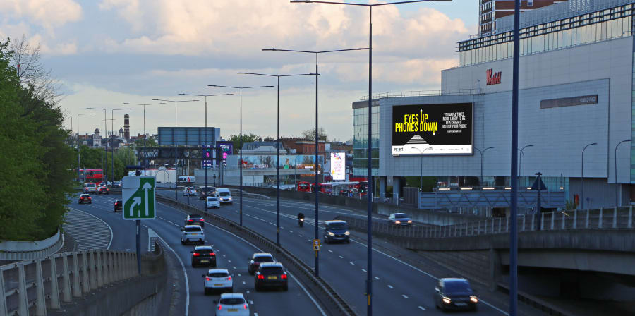 Image on a screen over a busy motorway